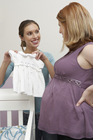 Two women looking at baby clothes by cradle