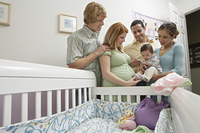 Two couples and baby (1-6 months) by cradle
