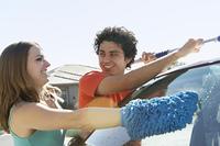 Young couple washing car