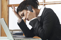 Business woman using mobile phone at desk in office