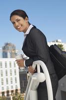 Businesswoman leaning on railing outdoors, portrait