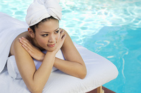 Young Chinese woman lying by swimming pool