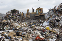 Digger moving waste at landfill site