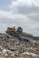 Digger working at landfill site