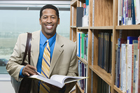 Business man standing by bookshelf, portrait