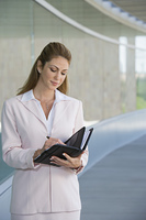 Businesswoman writing in planner outdoors