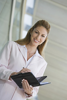 Businesswoman writing in planner outdoors, portrait
