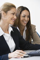 Two businesswoman smiling over computer