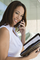 Woman using cell phone holding planner, portrait