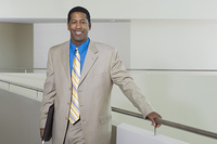 Business man standing by balustrade in office building, portrait