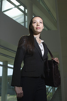 Business woman with handbag standing in office building, low angle view