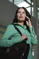 Business woman using mobile phone indoors, low angle view
