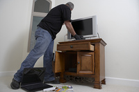 Burglar stealing television from house