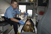 Paramedic taking care of victim in ambulance