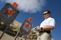 Man holding hand gun, near targets at firing range