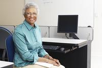 Female teacher holding book in computer classroom, portrait