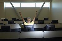 Mature female student celebrating in computer classroom