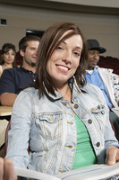 Portrait of female college student in classroom, others in classroom