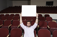 Male student holding blank board over head, in lecture theatre, portrait