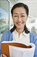 Woman embracing book at school, smiling, portrait