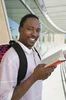 Male student holding book at school, smiling, portrait