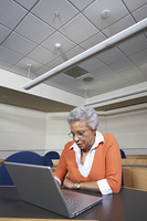 Mature female student using laptop in lecture theatre