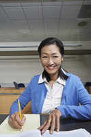 Mature female student working in lecture theatre, portrait