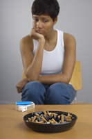 Woman staring at full ashtray of cigarettes on table
