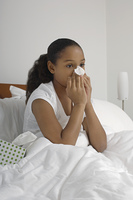 Girl (7-9) blowing nose in bed