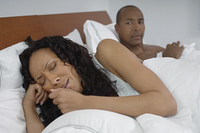 Man watching woman crying in bed