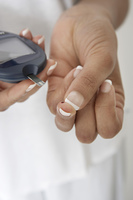 Woman taking diabetes test, close-up of hands