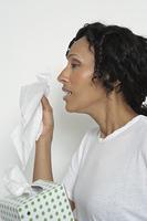 Woman holding box of tissues, studio shot