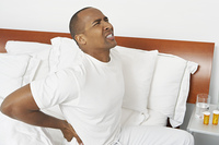 Man with bad back in hospital bed