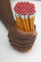 Person holding large group of pencils, close-up of hand