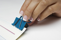 Woman holding binder clip, close-up of hand