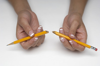 Woman holding broken pencil, close-up of hands