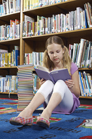Girl sitting on the floor and reading book in library