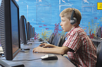 School boy wearing headphones in computer room
