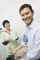 Doctor checking male patients blood pressure in hospital