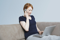 Woman using laptop and mobile phone on sofa