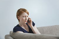 Woman talking on mobile phone on sofa