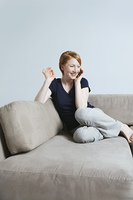 Woman talking on mobile phone on sofa