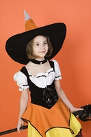 Girl (7-9) wearing witch costume for Halloween, studio shot