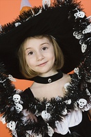 Portrait of girl (7-9) wearing witch costume for Halloween