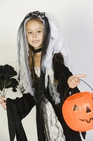 Portrait of girl (7-9) wearing Halloween costume with jack-o-lantern