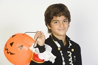 Portrait of boy (7-9) wearing Halloween costume, with jack-o-lantern