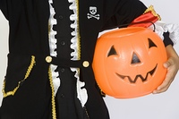 Boy (7-9) wearing Halloween costume, with jack-o-lantern