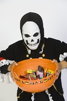 Portrait of boy (7-9) wearing skeleton mask, holding candy bowl