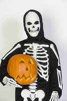 Portrait of child (7-9) wearing skeleton costume, with jack-o-lantern
