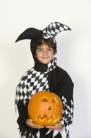 Portrait of boy (7-9) wearing jester costume, with jack-o-lantern